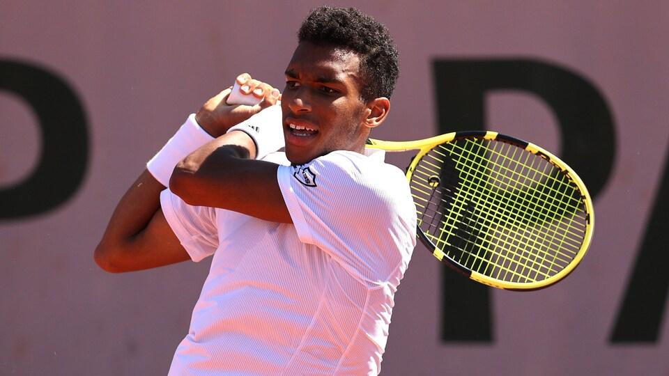 Un joueur de tennis vêtu de blanc regarde une balle frappée du revers avec une raquette jaune.