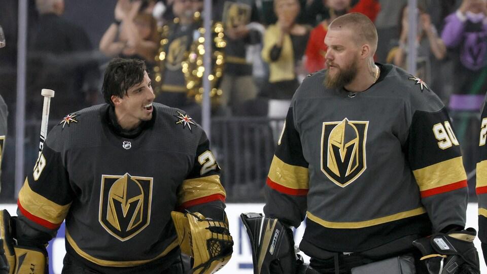Les deux gardiens, portant leur équipement sauf leur casque, se regardent en souriant pendant un échauffement durant la série contre le Wild du Minnesota.