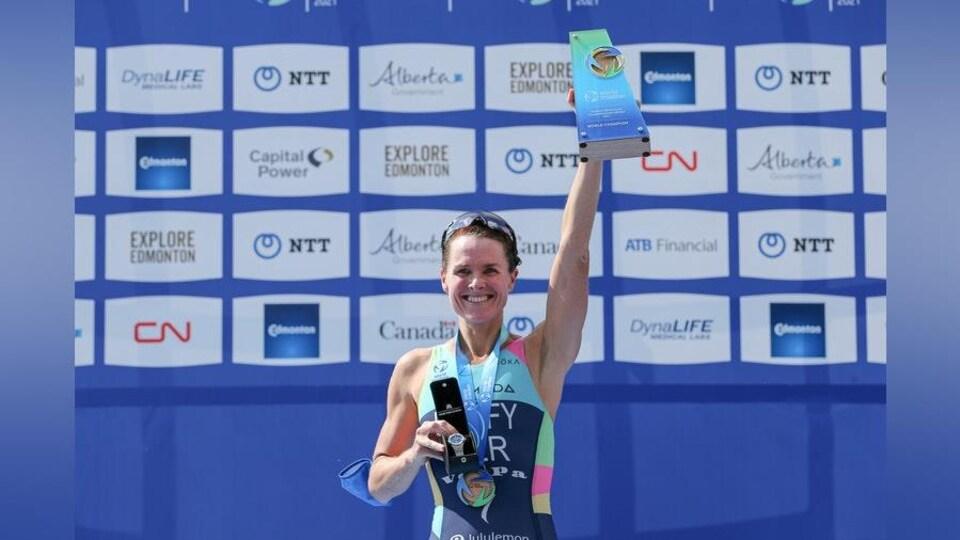 Elle tient son trophée dans sa main gauche levée.