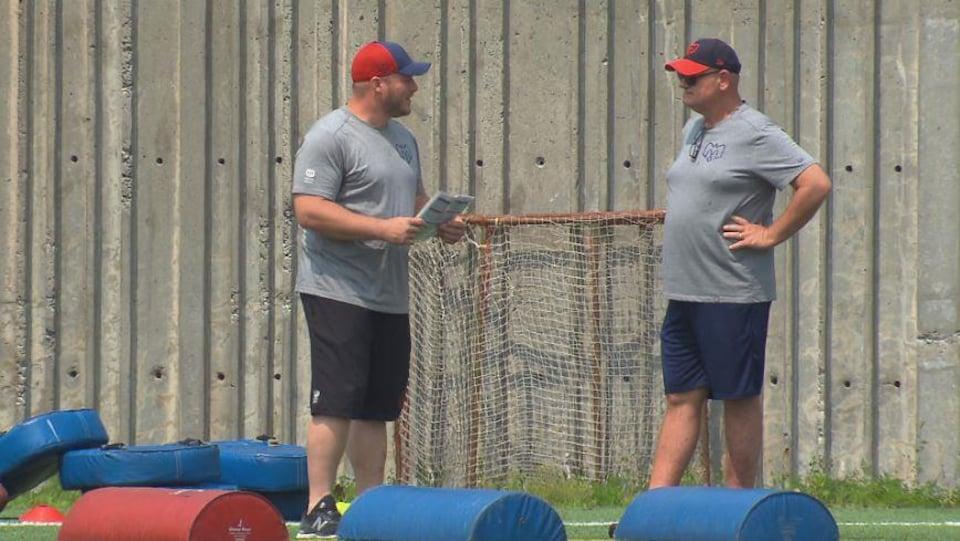 Ils discutent sur le terrain d'entraînement.