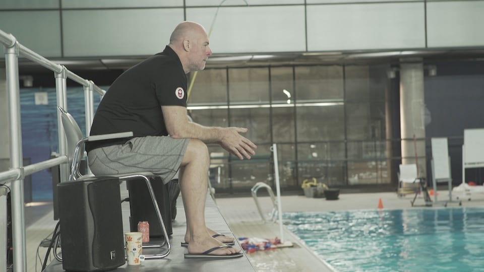 Un homme est assis sur le bord d'une piscine.