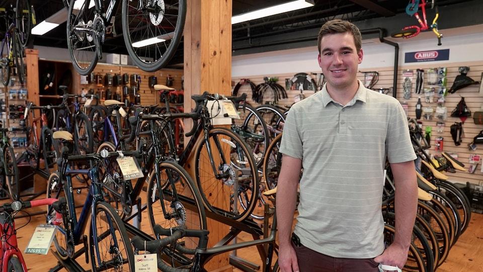 Un homme regarde la caméra devant des supports à vélos.