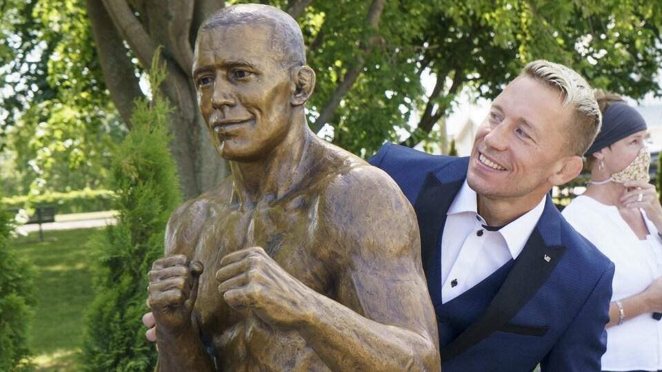 Un homme en complet pose à côté d'une statue de bronze à son image.