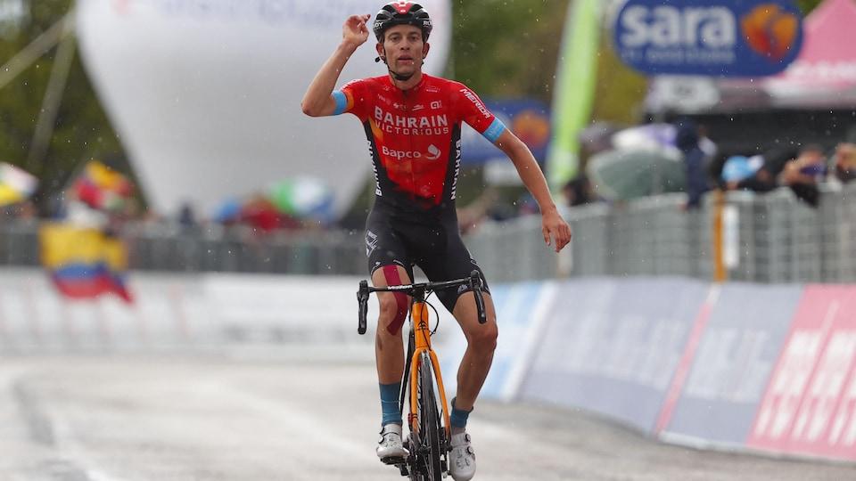Le cycliste lève le bras droit dans les airs en franchissant la ligne d'arrivée sous la pluie.