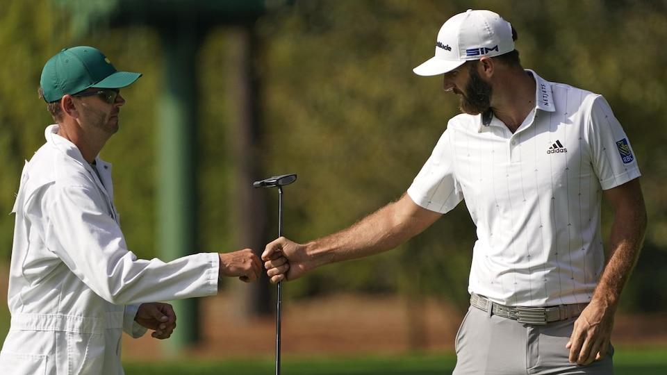 Un golfeur est félicité par son cadet vêtu d'une salopette blanche.