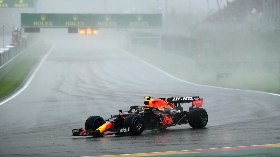 Il prend un virage au volant de sa voiture, sous la pluie.
