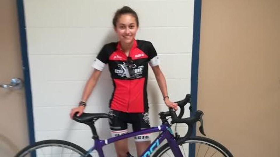 Une jeune fille en habit de cycliste pose devant un vélo de route.