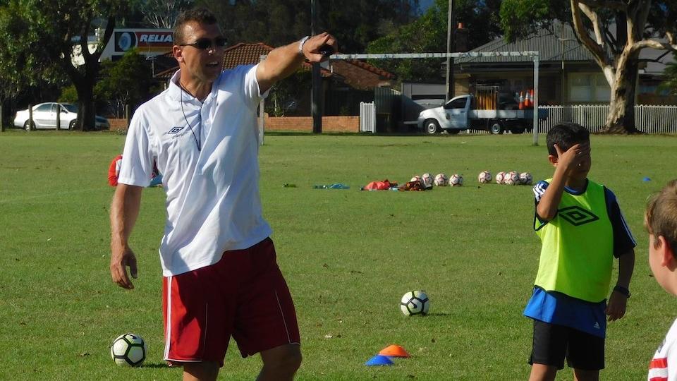 Un entraîneur de soccer, vêtu de blanc, donne des indications à des enfants lors d'une séance sur un terrain gazonné.