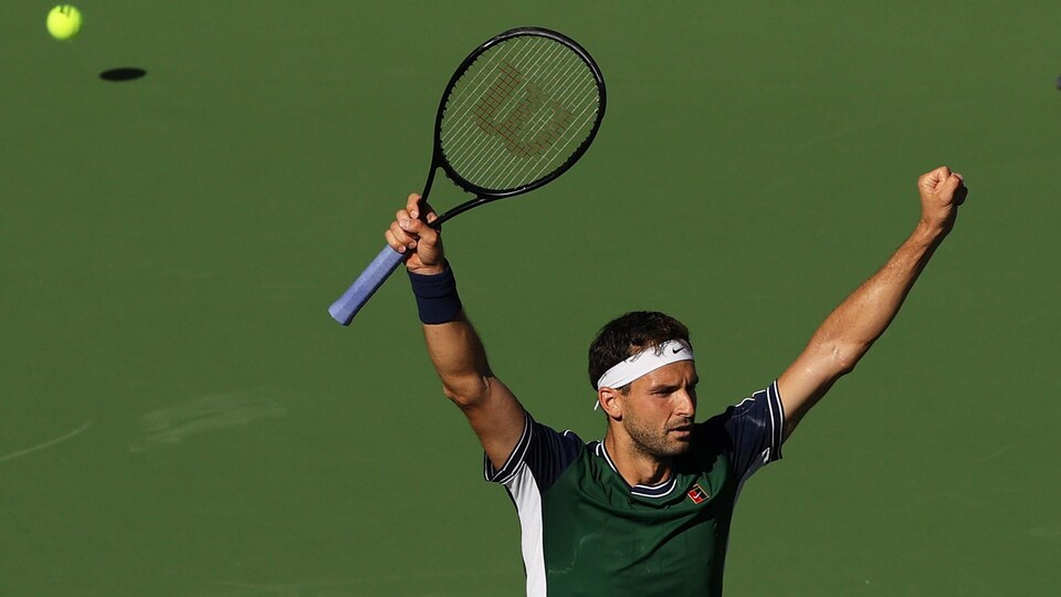 Le joueur de tennis Grigor Dimitrov lève les mains dans les airs après avoir gagné son match de tennis.