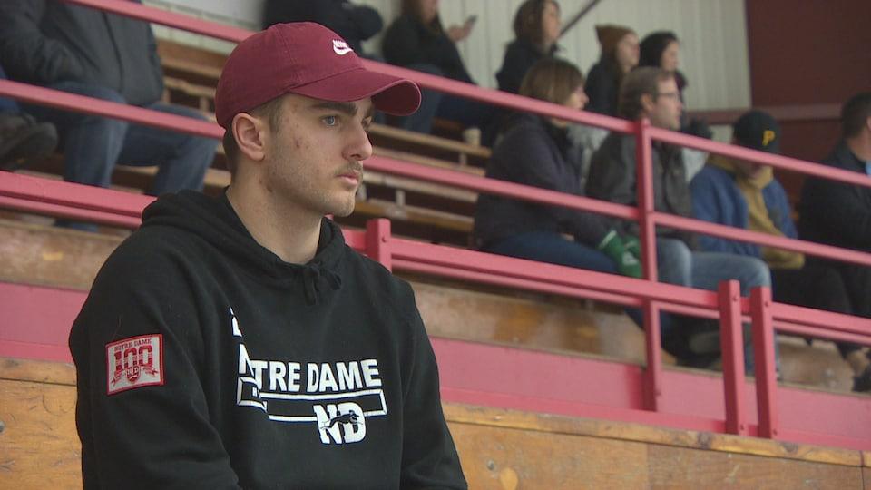 Guillaume St-Onge, portant un coton ouaté aux couleurs de son équipe, dans les gradins de l'aréna.