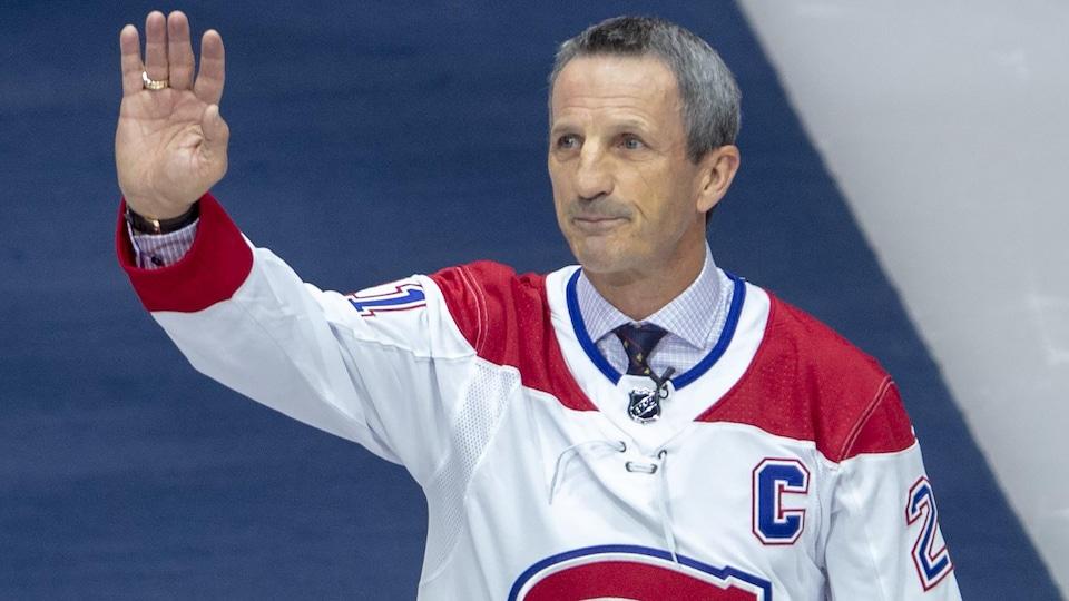 Guy Carbonneau, avec son chandail de capitaine, salue la foule du Centre Bell en levant le bras droit.