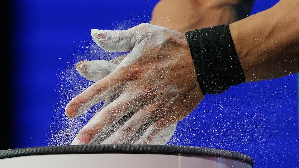Un athlète met de la craie sur ses mains avant de soulever une barre.