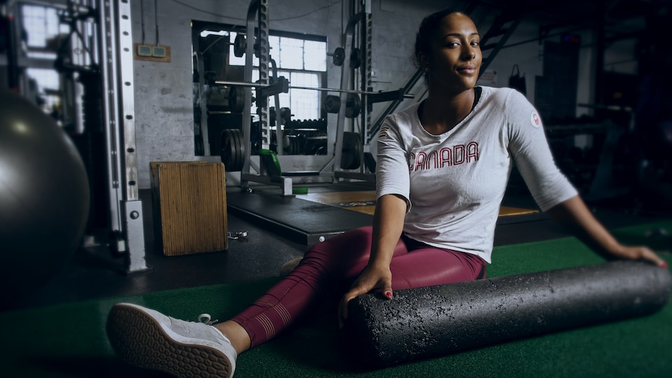 Kristen Ngarlem est assise par terre dans sa salle d'entraînement.