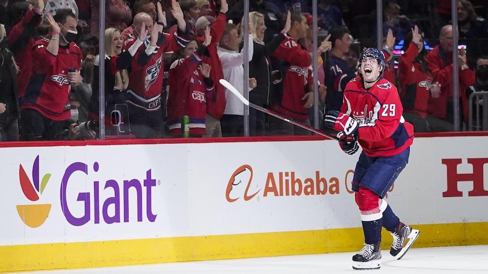 Sous les acclamations de la foule, l'attaquant québécois sourit à pleines dents et regarde le tableau indicateur après avoir marqué son premier but dans la LNH.