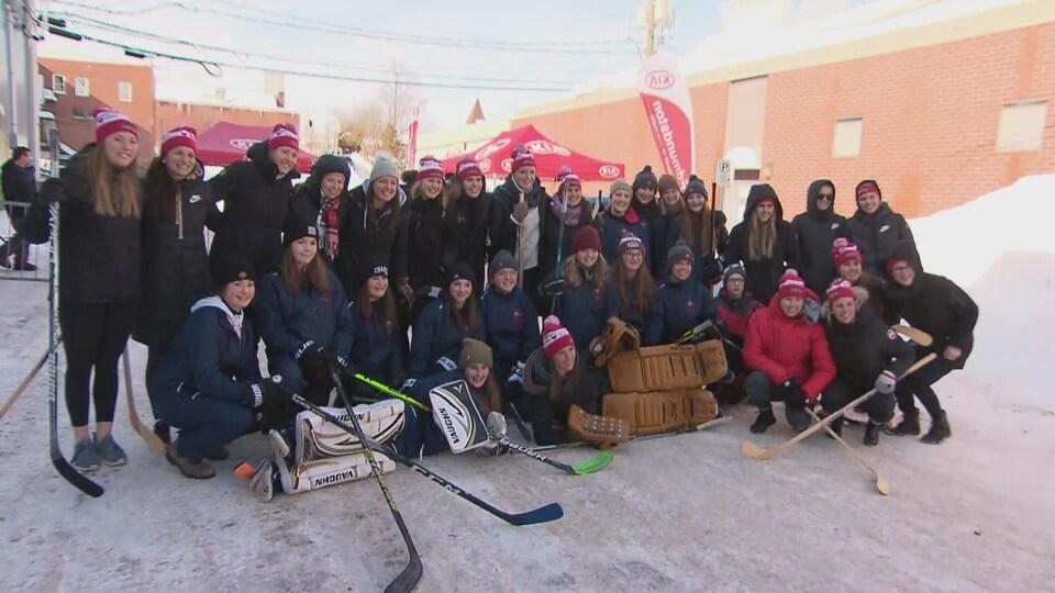 Des joueuses de hockey-balle, ensemble, posent pour une photo dehors.