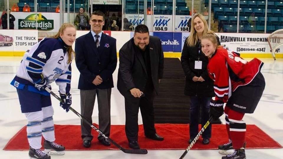 Mise au jeu officielle, avec deux joueuses de hockey face à face.
