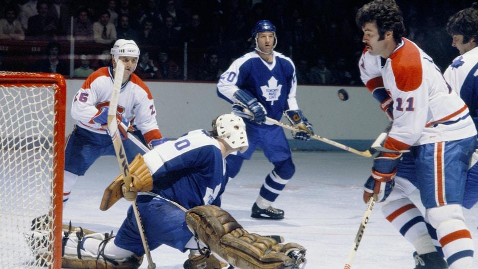 Un gardien fait le grand écart sur la patinoire à côté de joueurs adverses.