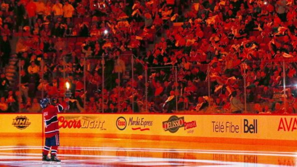 Le flambeau du Canadien porté par un jeune garçon sur la patinoire du Centre Bell.