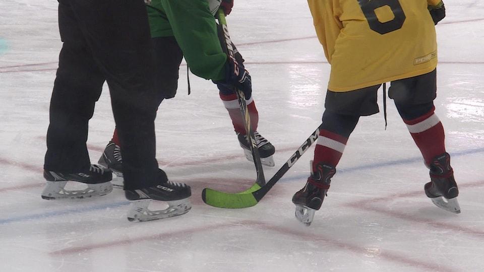 Deux joueurs de hockey attendent que l'arbitre dépose la rondelle sur la patinoire