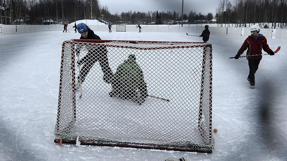 À travers un grillage, des jeunes hockeyeurs s'amusent sur une patinoire extérieure.