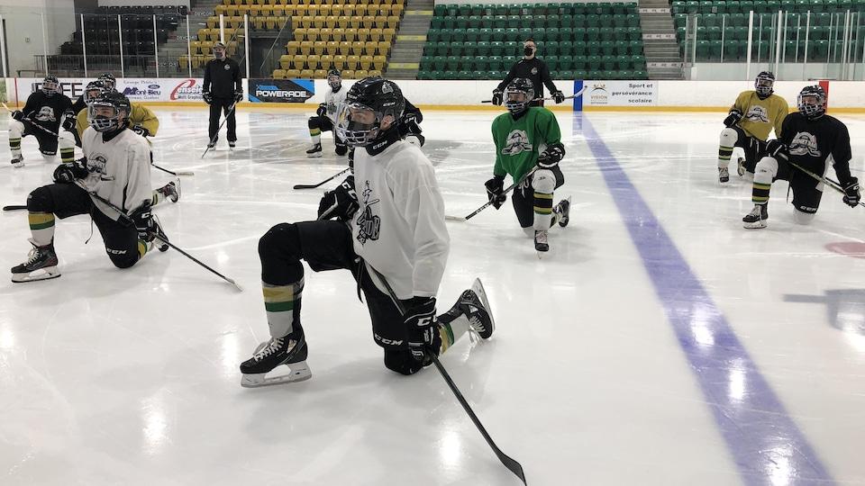 Des joueurs de hockey écoutent les directives de leur entraîneur.