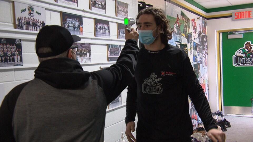Un joueur fait prendre sa température à son arrivée à l'aréna.