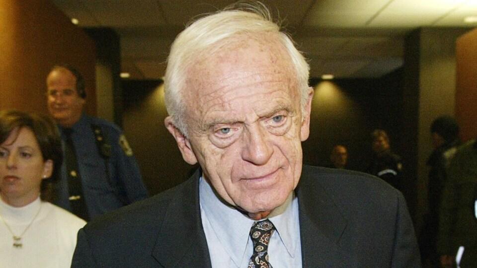 Un homme aux cheveux blancs et en complet cravate.