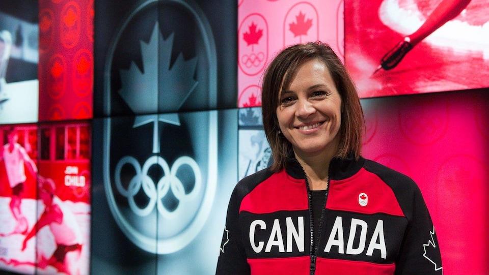Elle porte une veste de l'équipe canadienne et sourit.