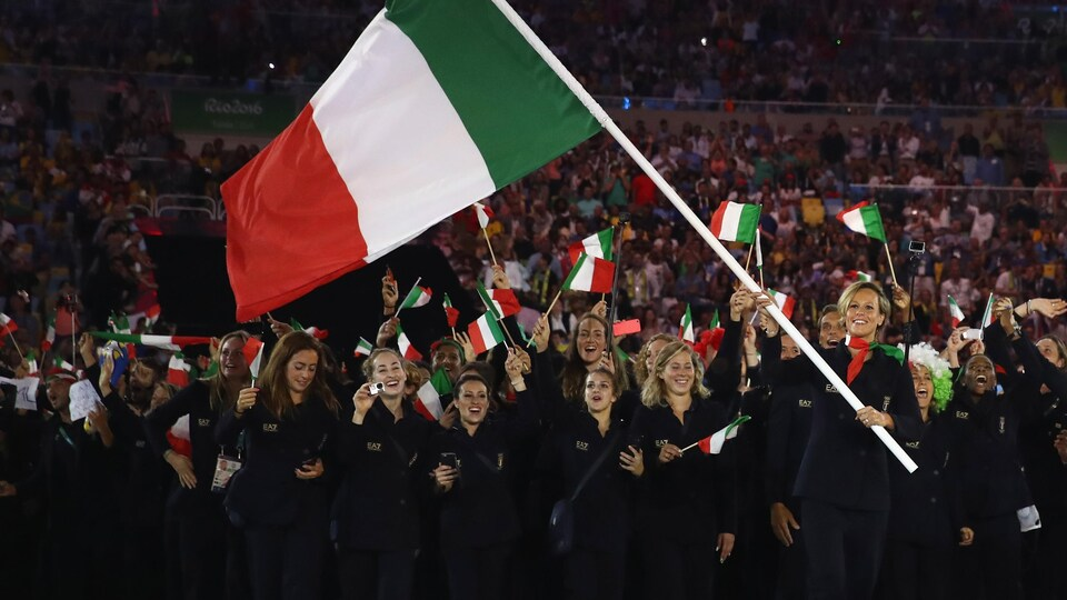 Elle marche avec un grand drapeau de son pays.
