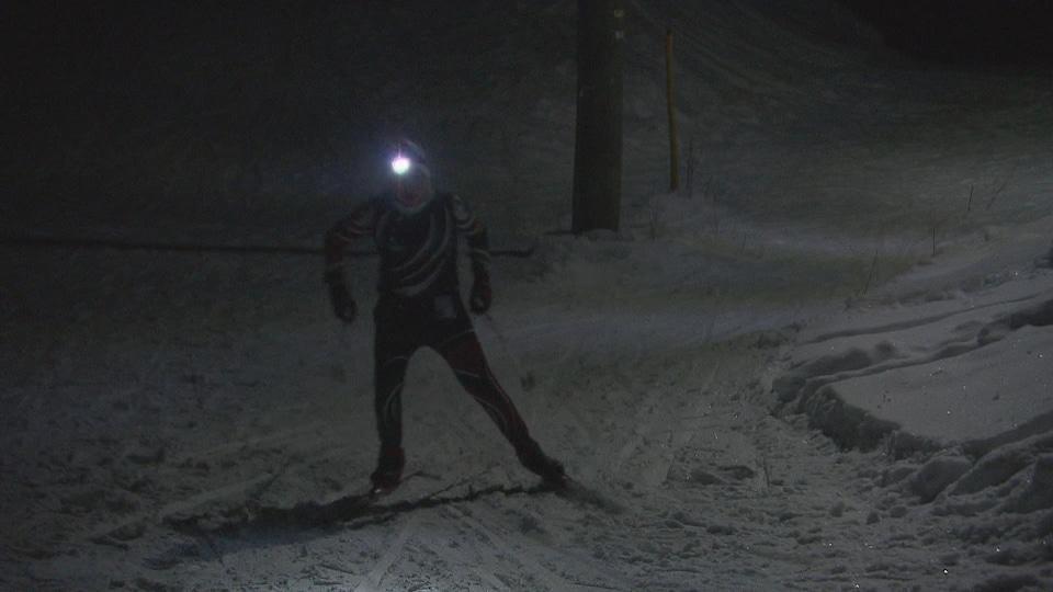 Un skieur dans la nuit avec une lumière sur la tête.