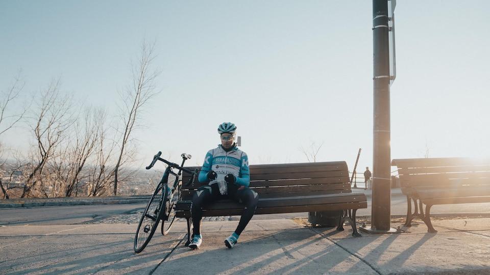 Il est assis sur un banc.