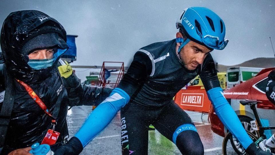 Le cycliste prend la bouteille que lui remet un membre de son équipe.