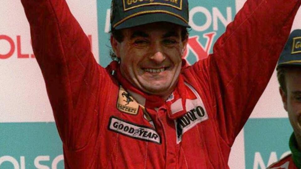 Jean Alesi, heureux, lève les bras, poings serrés, sur le podium du Grand Prix du Canada de 1995.