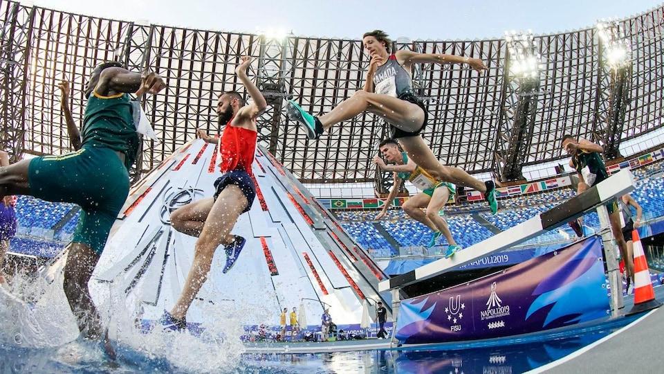 Jean-Simon Desgagnés en plein saut par dessus une barrière et un obstacle d'eau.