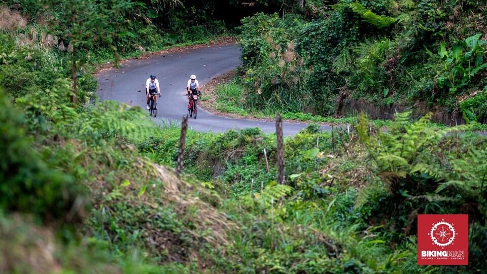 Deux hommes pédalent sur une route au cœur de la jungle de l'île de Taïwan.