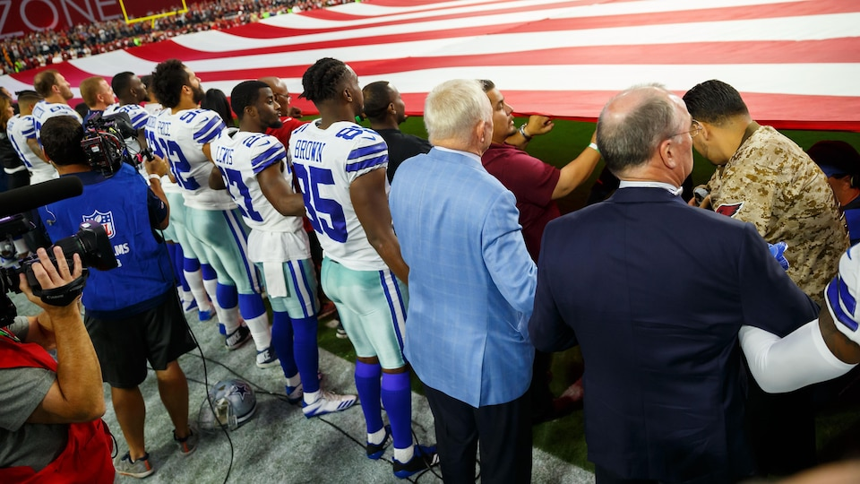 Sep 25, 2017; Glendale, AZ, USA; Dallas Cowboys owner Jerry Jones (blue) locks arms with his players on the sidelines during the national anthem prior to the game against the Arizona Cardinals at University of Phoenix Stadium. Mandatory Credit: Mark J. Rebilas-USA TODAY Sports - 10308262