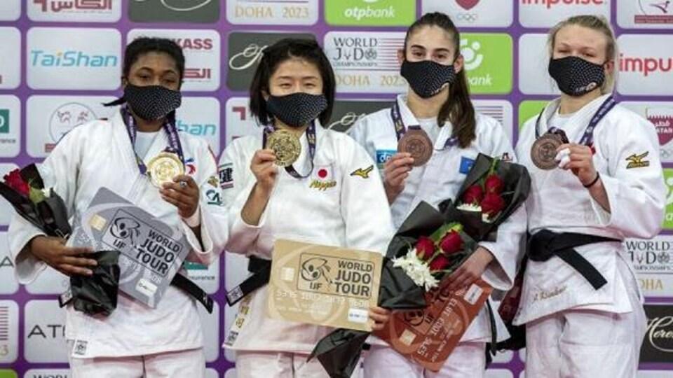 Quatre judokas, masquées sur un podium, posent avec leur médaille au cou.