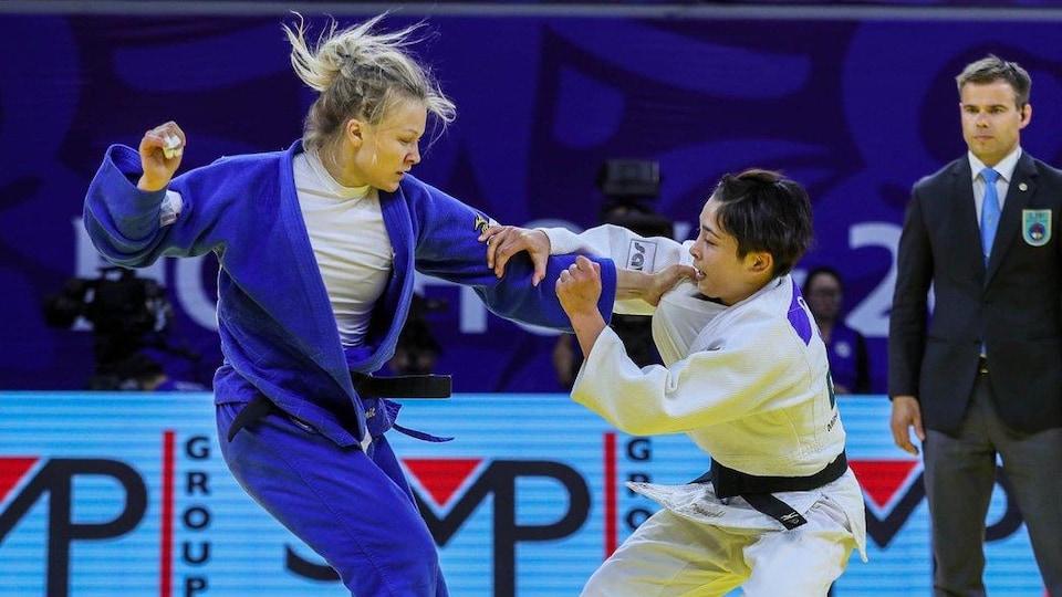 Une judoka tente d'en projeter une autre au sol.