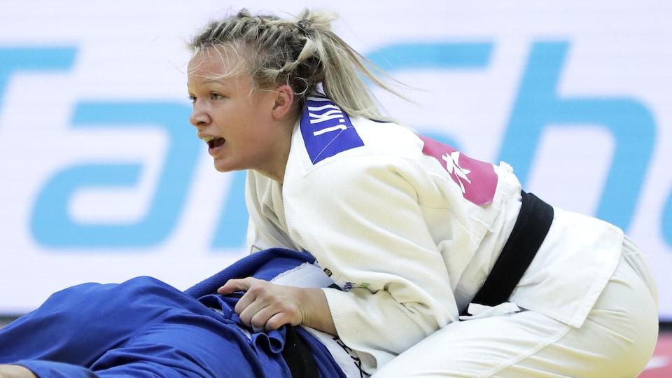 Elle attrape son adversaire par la ceinture et réagit pendant un combat.