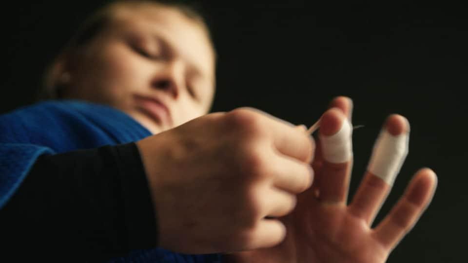 Elle met du ruban sur ses doigts.
