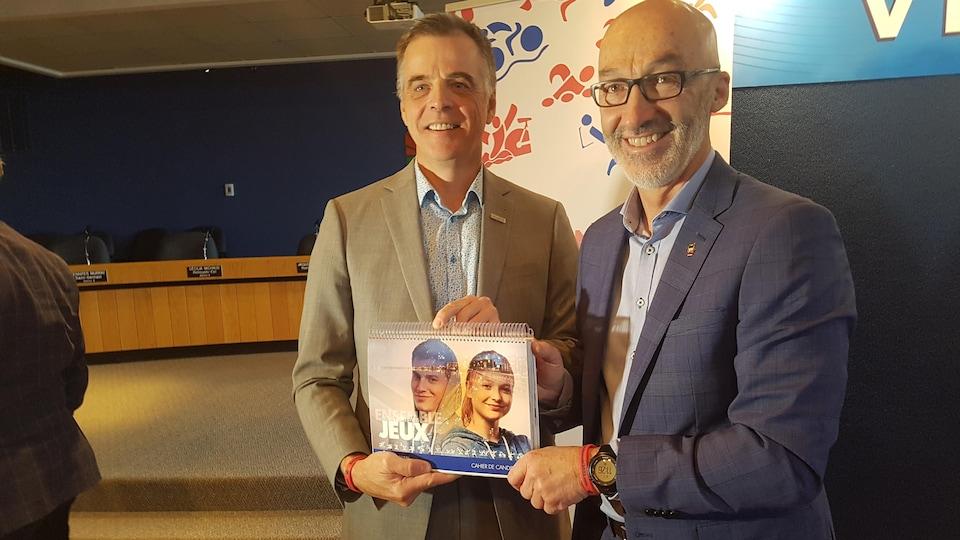 José Arsenault et Marc Parent tenant le cahier de candidature, debout devant les médias