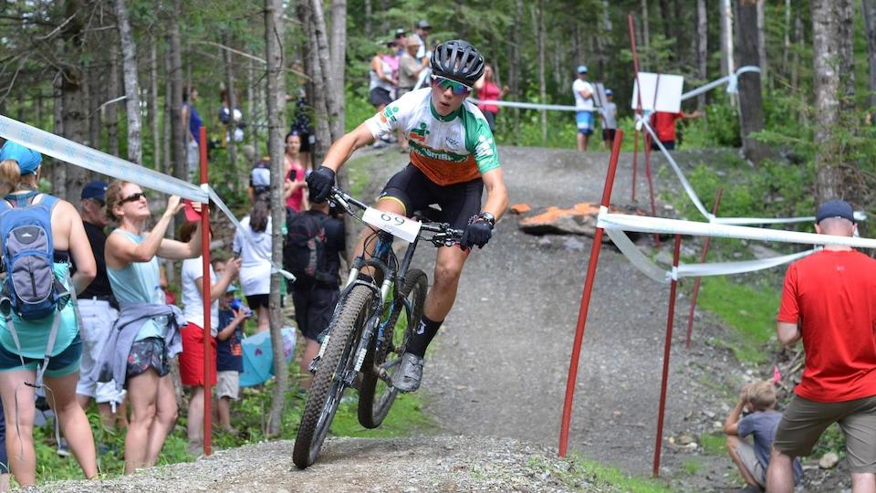 Un athlète en vélo de montagne dans un sentier bordé de spectateurs.