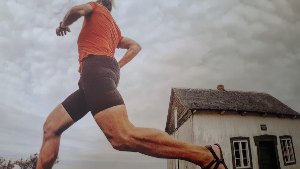 Un homme court devant une petite maison en bordure du fleuve Saint-Laurent.