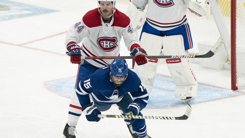 Le défenseur repousse un joueur des Maple Leafs loin du filet.