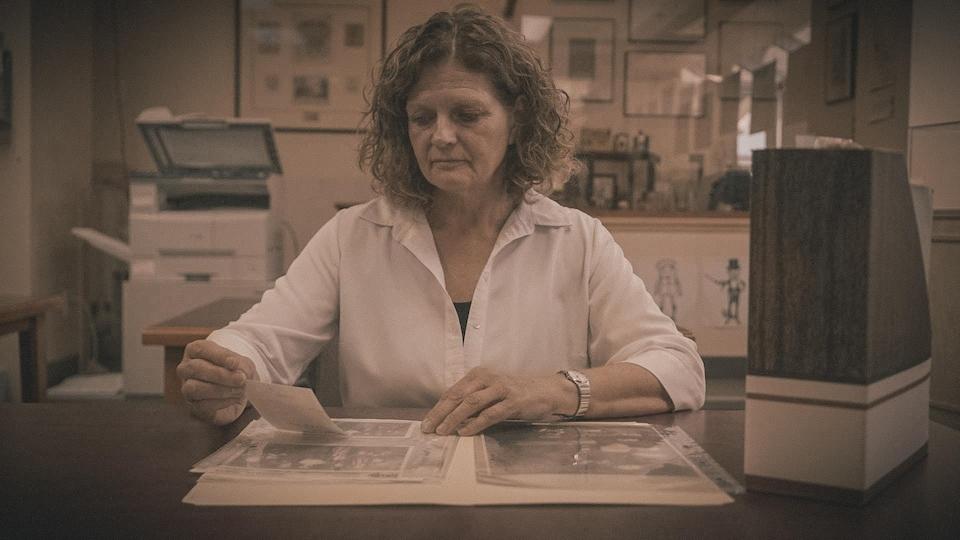 Une femme regarde à son bureau de vieilles photos