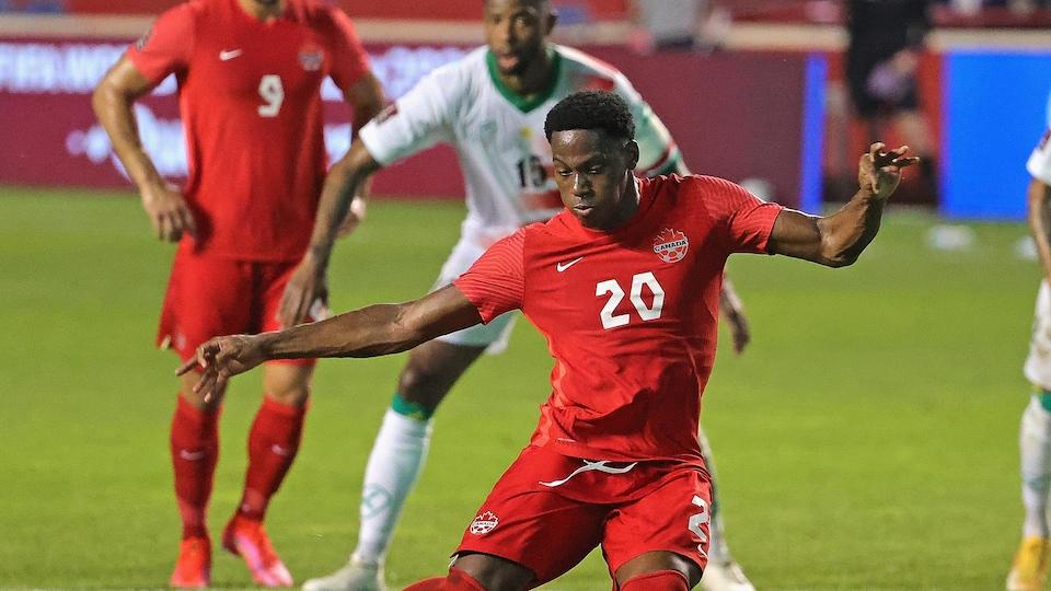 Le joueur canadien s'élance sur un tir de pénalité, le ballon sur le point d'être frappé par son pied droit.