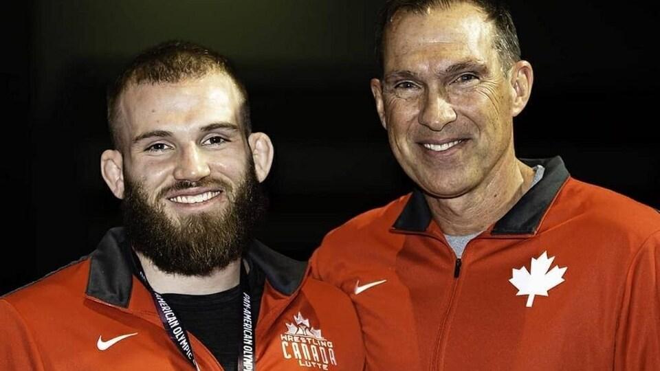 Deux hommes en rouge sourient.