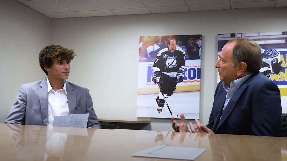 Josh Richards et Gary Bettman discutent autour d'une table dans les bureaux de la LNH.
