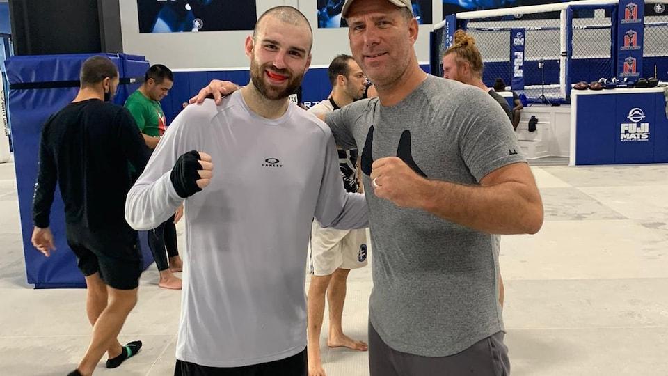 Deux hommes posent pour la caméra dans un centre d'entraînement d'arts martiaux mixtes.