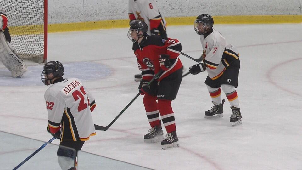 Joueur de hockey debout devant le filet avec des adversaires derrière et devant lui.